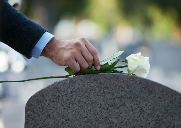 Placing flower on grave stone