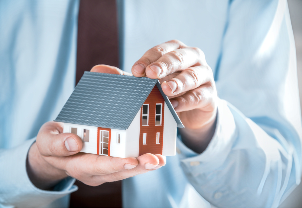 Close up Businessman in Business Suit Holding a Cute Miniature House Model Using his Both Hands.